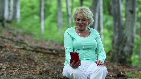 Woman sits on a fallen tree in the forest and communicates via his smartphone Footage