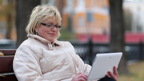 Woman sits on the bench near the road and uses tablet computer Live Action