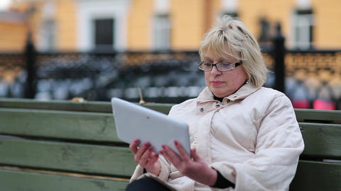 Blonde woman with tablet computer sits on the bench Footage
