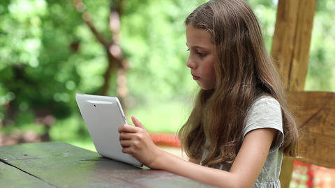 Beautiful girl with white tablet computer sits at the table Live Action