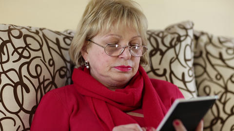 Woman reads a book. Senior woman sits on a sofa and reads electronic book Footage