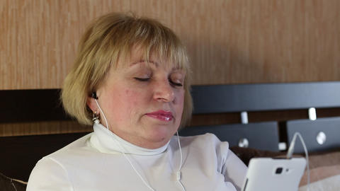 Senior woman with closed eyes sits on the sofa and listens to music Footage