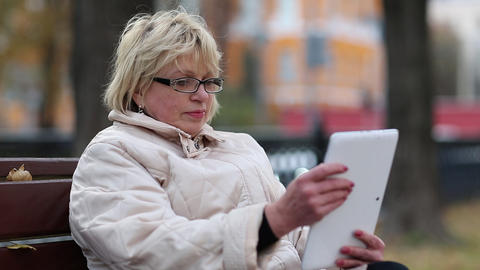 Blonde woman sits on the bench near the road and uses Tablet PC Footage