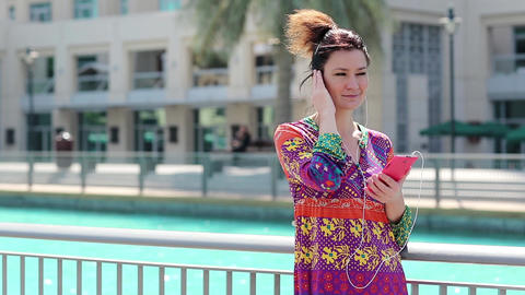 Woman with red smartphone and earphones listens to music Live Action