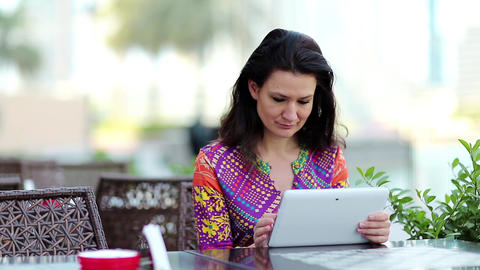 Woman with white tablet computer sits at a table in a cafe Live Action