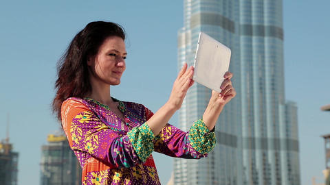 Attractive woman stands near skyscraper and makes photos on his Tablet PC Footage
