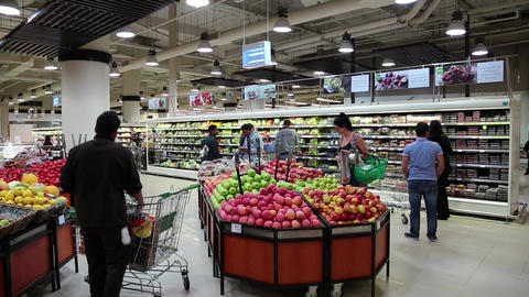 People near shop counter with fruits inside Dubai Mall, United Arab Emirates Footage