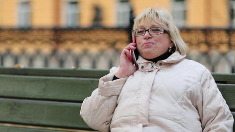 Blonde woman sits on the bench and talks on the phone Footage