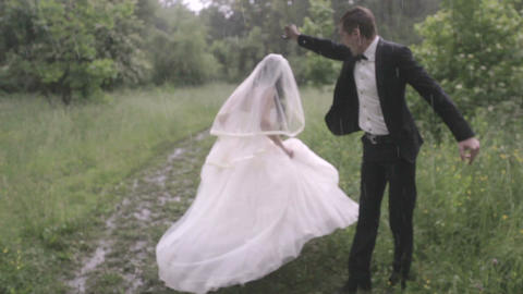 Happy and happy newlyweds with umbrella in the rain Live Action