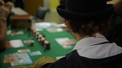 Friends in fancy dresses playing board game with cards, cool costume party Footage
