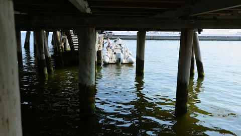Motorboat moored at old wooden pier, people leaving boat after fishing tour Footage