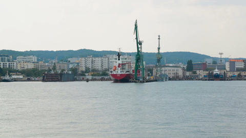 Industrial zone of seaside city with cranes and cargo ships, view from sea Footage