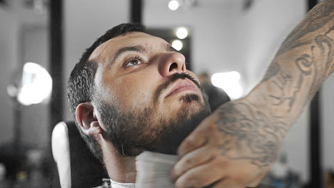 Barber whisks away sheared hairs from customer's shoulders by brush, tattoed ビデオ