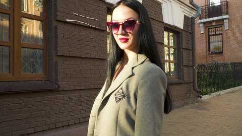 Stylish young woman in sunglasses and coat against brown building at the street Footage