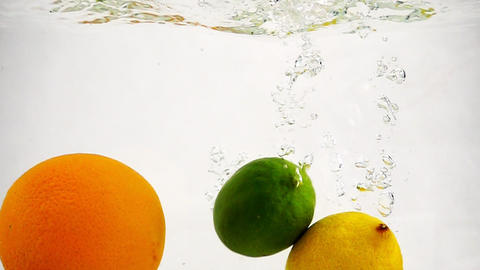 Lemon, orange and lime fall in water. Slow motion fruit with bubbles on isolated Archivo