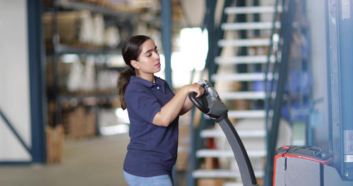 Female working in warehouse using forklift truck Live Action