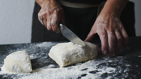 Women's hands cut the dough into pieces with kitchen knife Footage