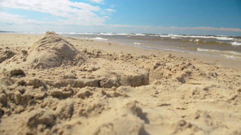 Lone sandcastle fort pyramid closeup on the sunny beach minimalistic background Footage
