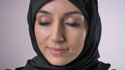 Young muslim girl in hijab opens eyes and watches at camera, dreaming concept Footage