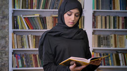 Young sweet muslim girl in hijab opens book, reads, religious concept, bookshelf Footage