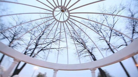 romantic gazebo in the park on a blue sky background GIF