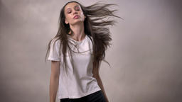 Young brunette girl is dancing and jumping, smiling, movement concept, grey Footage