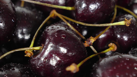 Cherry. Ripe cherries rotating over black background. Rotating Black Ripe Sweet Live Action