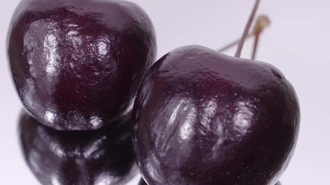 Cherry. Ripe cherries rotating over white background. Rotating Black Ripe Sweet Live Action