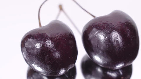 Cherry. Ripe cherries rotating over white background. Rotating Black Ripe Sweet Footage