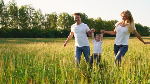 Happy family: Father, mother and son, running in the field dressed in white t Footage