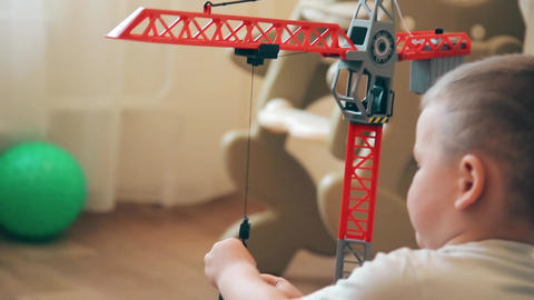 A little boy learns to lift and lower the load on the crane Footage