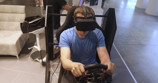 Man in VR headset game simulator car and plays racing Footage