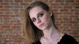 Young charming girl with smoky eyes is watching at camera, smiling, flirt Footage