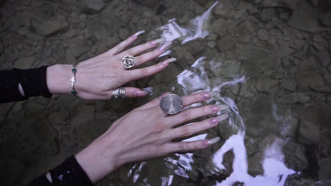 Female hands with long natural nails in the water of mountain creek GIF