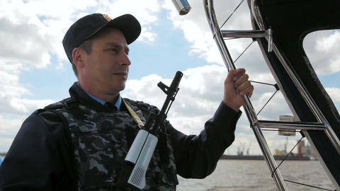 water policeman with gun patrols river on motorboat under blue sky Live Action