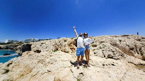 360 degree young couple rests on rocky ocean coast in summer Archivo