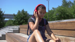 The girl listens to the music on the headphones saddle on the bench in the park Archivo
