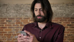 Young attractive brunette man with beard is watching in smartphone, watching at Footage