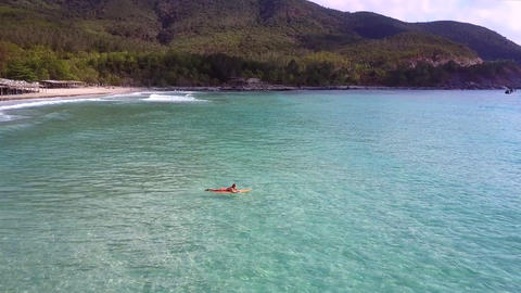 woman lies on surfboard floating in sea against green landscape 영상물