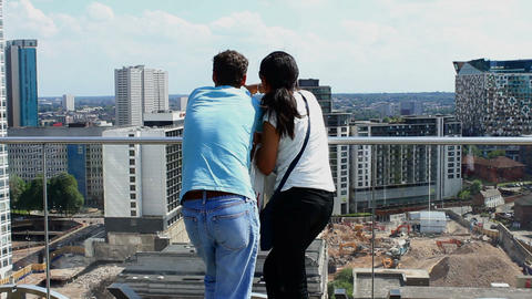 Loving Couple overlooking the cityscape. The girl showing him the views of city Footage