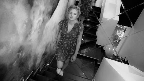 Young charming girl in dress and gumshoes stand at staircase Photo