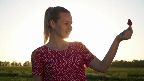 Pretty young girl holding strawberry at sunset background Footage