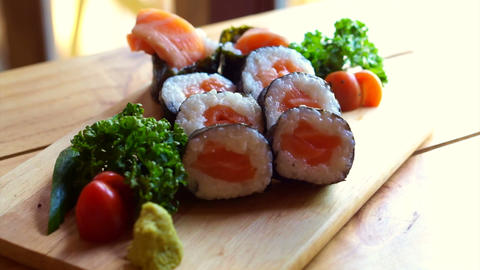 Salmon nori maki sushi beautiful display on wooden board. Japanese cuisine Footage