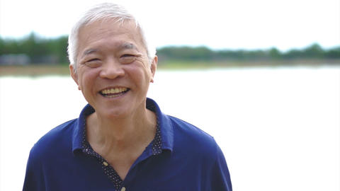Video of Happy asian senior man smiling happy in park with lake background Footage
