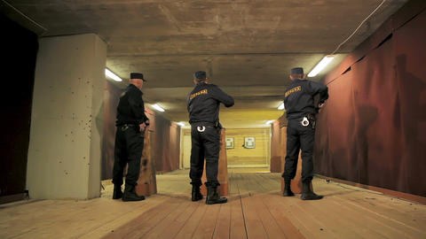 security men take pistols out of pockets to fire in shooting gallery GIF