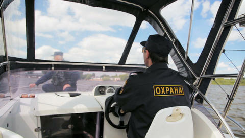water policeman operates security motorboat in cab watching colleague Footage