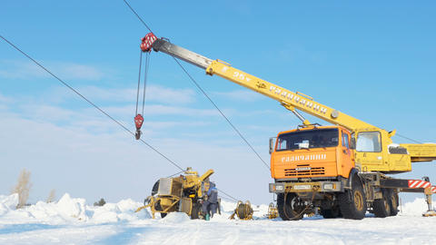 crane holds cable for high voltage line among snow under blue sky Footage