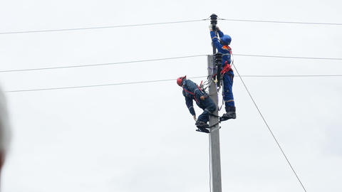 electrician stretches and fixes on colleague wire on pole using leg-irons Footage