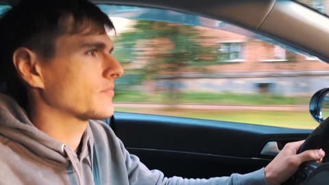 Handsome man driving a car, cityscape outside Live Action