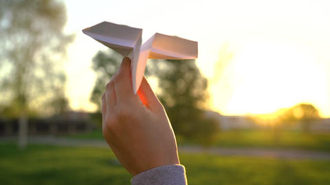 Hand launches paper airplane against sunset background. Slow motion Archivo